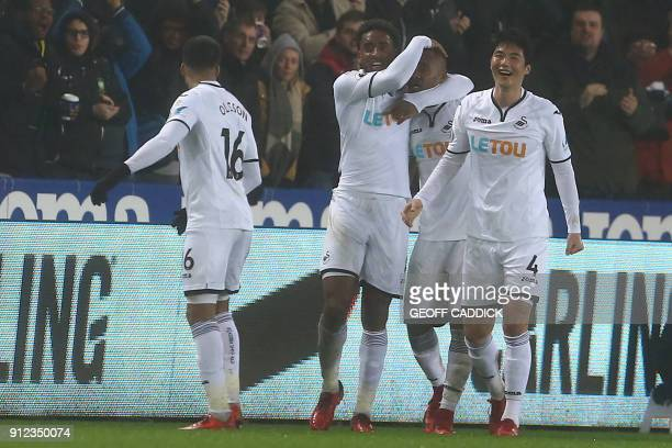 Swansea City's Ghanaian striker Jordan Ayew celebrates with teammates after scoring their second goal during the English Premier League football...