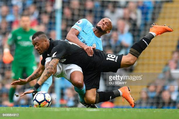 Swansea City's Ghanaian striker Jordan Ayew is tackled by Manchester City's Belgian defender Vincent Kompany during the English Premier League...