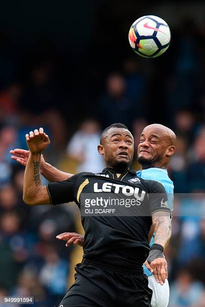 Swansea City's Ghanaian striker Jordan Ayew vies to head the ball with Manchester City's Belgian defender Vincent Kompany during the English Premier...