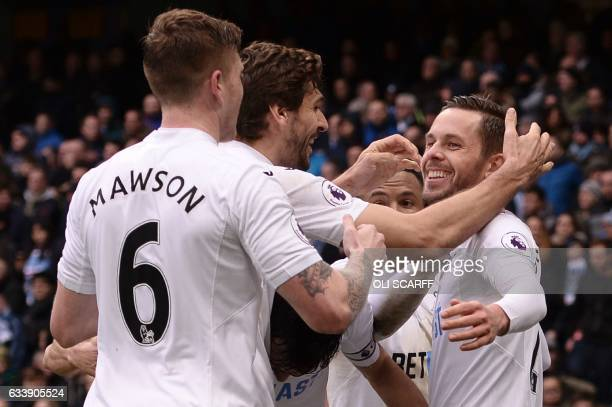 Swansea City's Icelandic midfielder Gylfi Sigurdsson celebrates with teammates after scoring their first goal during the English Premier League...