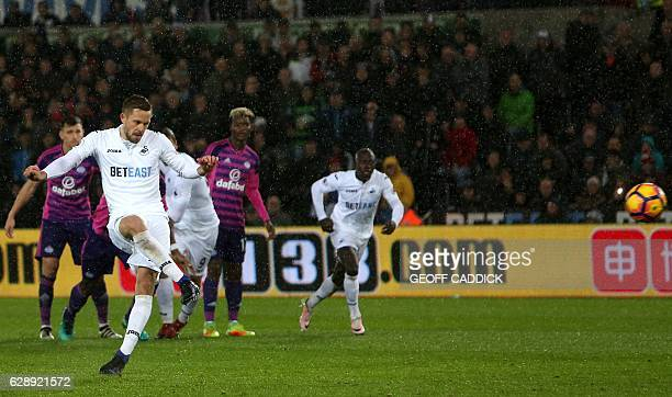 Swansea City's Icelandic midfielder Gylfi Sigurdsson scores the opening goal from the penalty spot during the English Premier League football match...
