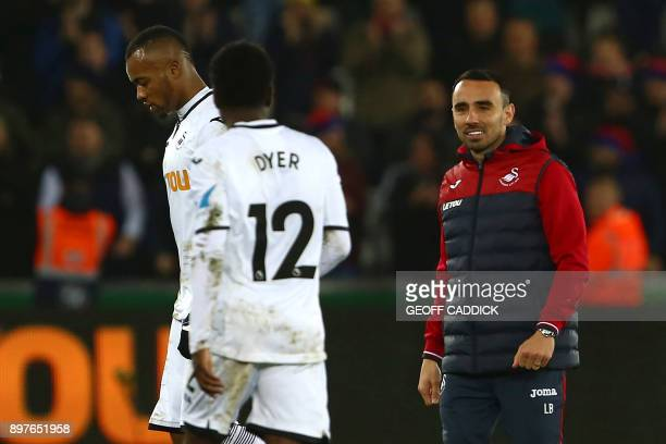 Swansea City's Interim manager Leon Britton congratulates his players on the pitch after the English Premier League football match between Swansea...