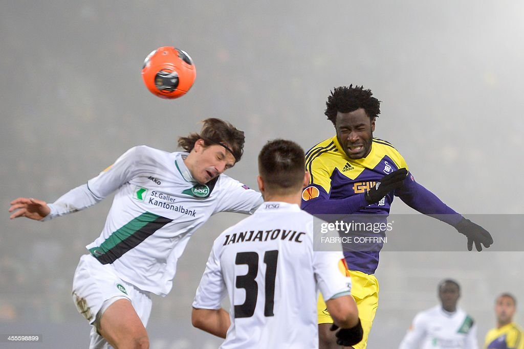 Swansea City's Ivorian striker Wilfried Bony (R) head the ball next to St Gallen's defender Daniele Russo (L) and his teammate German midfielder Dejan Janjatovic during the Europa League Group A football match between FC St Gallen and Swansea City on December 12, 2013 at the AFG Arena in St Gallen.