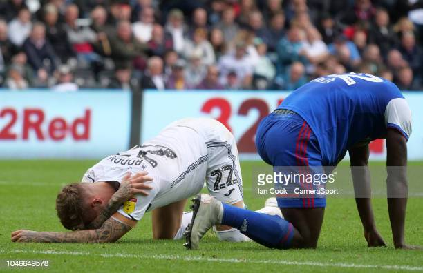 Swansea City's Joe Rodon goes down injured after a clash with Ipswich Town's Aristote Nsiala during the Sky Bet Championship match between Swansea...