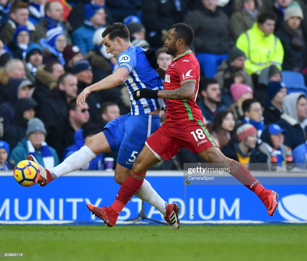 Swansea City's Jordan Ayew (right) vies for possession with Brighton & Hove Albion's Lewis Dunk (left) during the Premier League match between Brighton and Hove Albion and Swansea City at Amex Stadium on February 24, 2018 in Brighton, England.