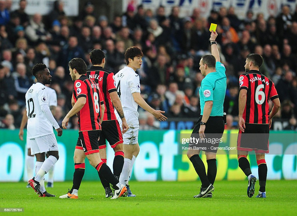 Swansea City's Ki Sung-Yueng is shown a yellow card by referee Kevin Friend during the Premier League match between Swansea City and AFC Bournemouth at Liberty Stadium on December 31, 2016 in Swansea, Wales.