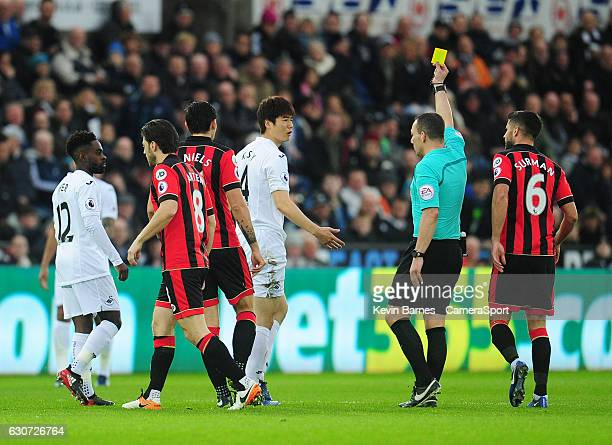 Swansea City's Ki SungYueng is shown a yellow card by referee Kevin Friend during the Premier League match between Swansea City and AFC Bournemouth...