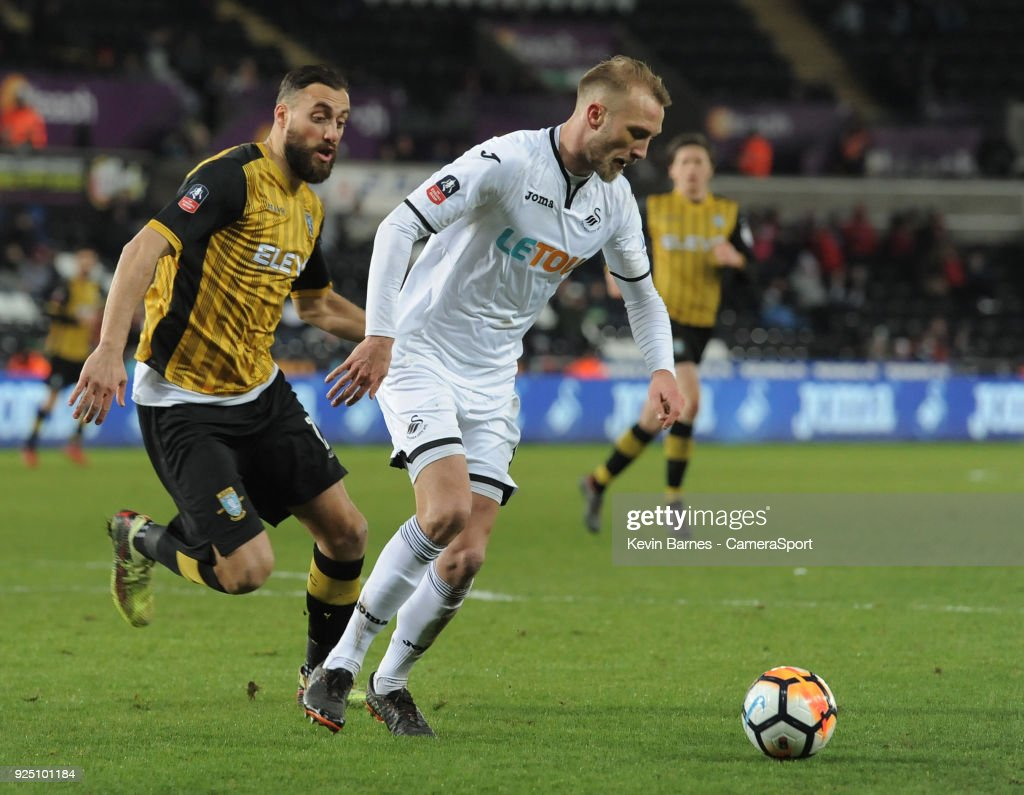 Swansea City's Mike van der Hoorn under pressure from Sheffield Wednesday's Atdhe Nuhiu during the The Emirates FA Cup Fifth Round Replay match between Swansea City and Sheffield Wednesday at Liberty Stadium on February 27, 2018 in Swansea, Wales.