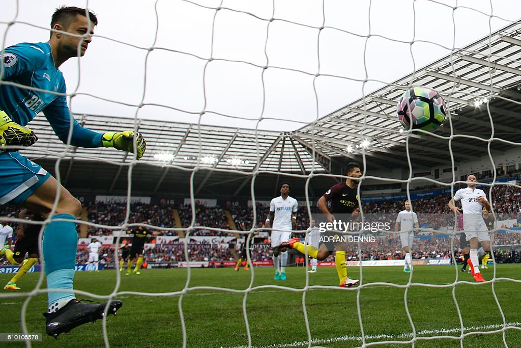 Swansea City's Polish goalkeeper Lukasz Fabianski (L) looks back to see the ball in his net after Manchester City's Argentinian striker Sergio Aguero (C) scored their second goal from the penalty spot during the English Premier League football match between Swansea City and Manchester City at The Liberty Stadium in Swansea, south Wales on September 24, 2016. / AFP / Adrian DENNIS / RESTRICTED TO EDITORIAL USE. No use with unauthorized audio, video, data, fixture lists, club/league logos or 'live' services. Online in-match use limited to 75 images, no video emulation. No use in betting, games or single club/league/player publications. /