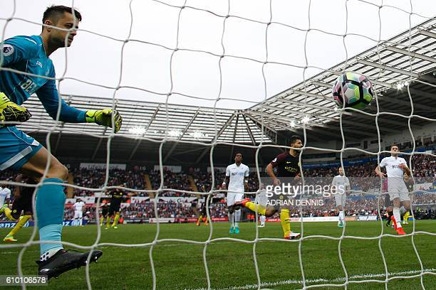 Swansea City's Polish goalkeeper Lukasz Fabianski looks back to see the ball in his net after Manchester City's Argentinian striker Sergio Aguero...