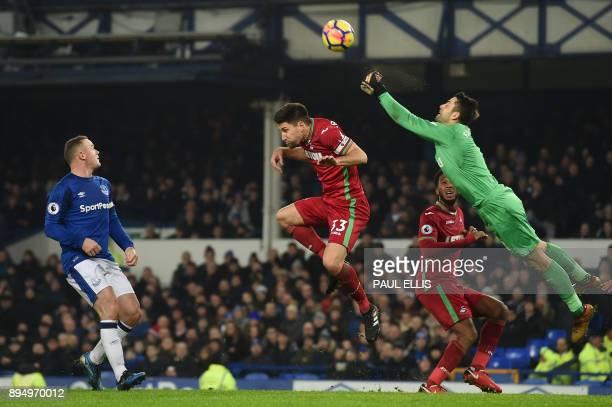 TOPSHOT Swansea City's Polish goalkeeper Lukasz Fabianski punches the ball clear as Everton's English striker Wayne Rooney watches during the English...