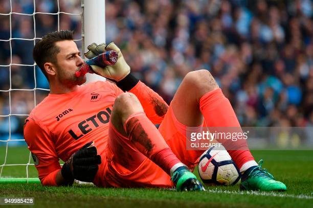 Swansea City's Polish goalkeeper Lukasz Fabianski takes a drink before restarting during the English Premier League football match between Manchester...