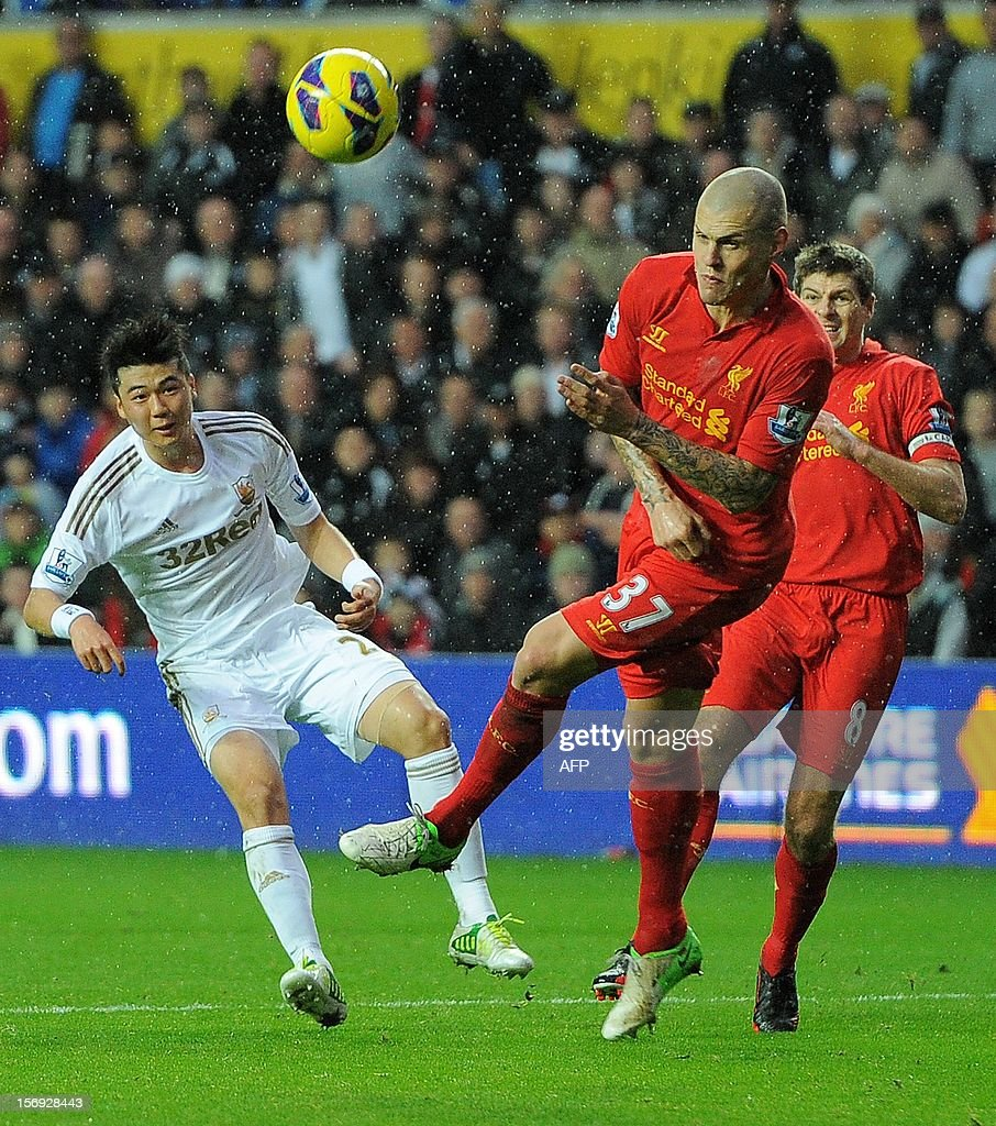 """Swansea City's South Korean midfielder Ki Sung-Yueng (L) shoots past Liverpool's Slovakian defender Martin Skrtel (C) during the English Premier League football match between Swansea City and Liverpool at The Liberty stadium in Swansea, south Wales on November 25, 2012. The match ended in a goal-less draw. AFP PHOTO/ANDREW YATES. RESTRICTED TO EDITORIAL USE. No use with unauthorized audio, video, data, fixture lists, club/league logos or """"live"""" services. Online in-match use limited to 45 images, no video emulation. No use in betting, games or single club/league/player publications."""
