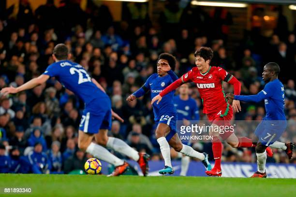 Swansea City's South Korean midfielder Ki SungYueng vies with Chelsea's Danish defender Andreas Christensen Chelsea's Brazilian midfielder Willian...