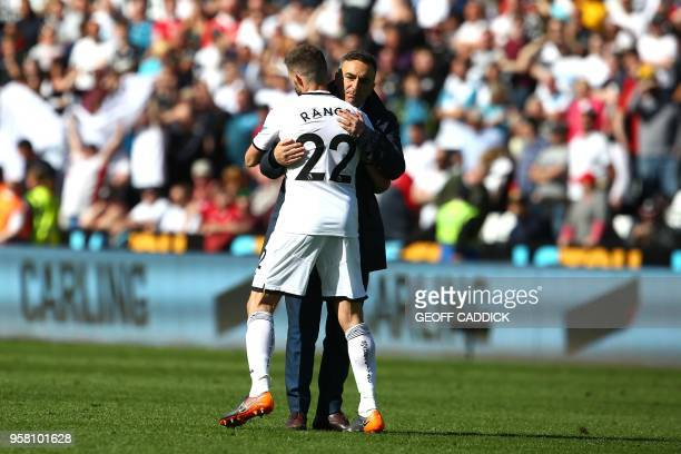 Swansea City's Spanish defender Angel Rangel embraces Swansea City's Portuguese manager Carlos Carvalhal after losing the English Premier League...