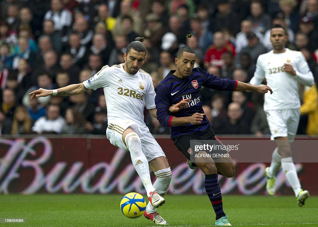 """Swansea City's Spanish defender Chico Flores (L) vies for the ball against Arsenal's Theo Walcott (2nd R) during the FA Cup third round football match at the Liberty Stadium in Swansea, Wales, on January 6, 2013. The game ended with a 2-2 draw. USE. No use with unauthorized audio, video, data, fixture lists, club/league logos or """"live"""" services. Online in-match use limited to 45 images, no video emulation. No use in betting, games or single club/league/player publications"""