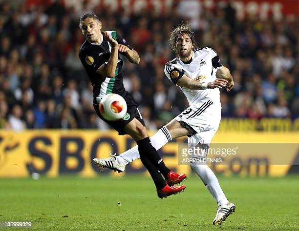 Swansea City's Spanish midfielder Miguel Michu shoots at goal past FC St Gallen's Luxembourger midfielder Mario Mutsch during the Europa League Group...