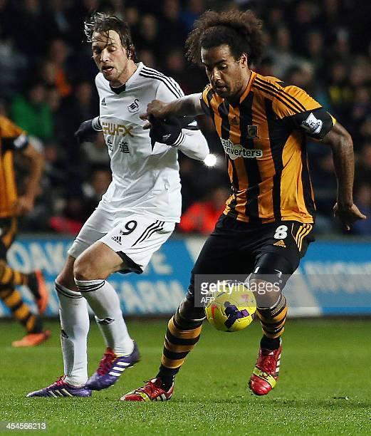 Swansea City's Spanish midfielder Miguel Michu vies with Hull City's British midfielder Tom Huddlestone during a Premier League football match...