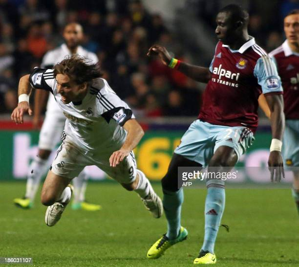 Swansea City's Spanish midfielder Miguel Michu vies with West Ham United's Senegalese midfielder Mohamed Diame during the English Premier League...