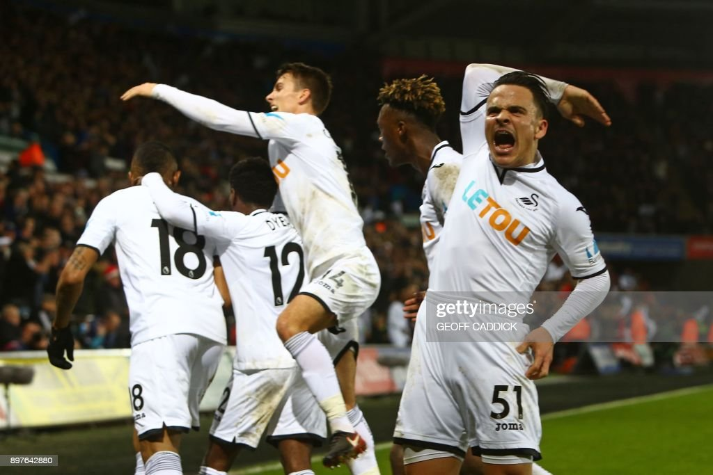 Swansea City's Spanish midfielder Roque Mesa (R) reacts as Swansea City's Ghanaian striker Jordan Ayew celebrates with teammates after scoring their first goal during the English Premier League football match between Swansea City and Crystal Palace at The Liberty Stadium in Swansea, south Wales on December 23, 2017. / AFP PHOTO / Geoff CADDICK / RESTRICTED TO EDITORIAL USE. No use with unauthorized audio, video, data, fixture lists, club/league logos or 'live' services. Online in-match use limited to 75 images, no video emulation. No use in betting, games or single club/league/player publications. /