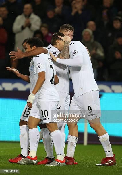 Swansea City's Spanish striker Fernando Llorente celebrates with teammates after scoring their third goal during the English Premier League football...
