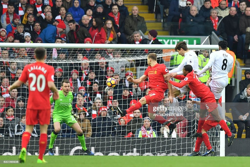 Swansea City's Spanish striker Fernando Llorente (3R) rises high to head the ball and score their second goal during the English Premier League football match between Liverpool and Swansea City at Anfield in Liverpool, north west England on January 21, 2017. / AFP / Anthony DEVLIN / RESTRICTED TO EDITORIAL USE. No use with unauthorized audio, video, data, fixture lists, club/league logos or 'live' services. Online in-match use limited to 75 images, no video emulation. No use in betting, games or single club/league/player publications. /