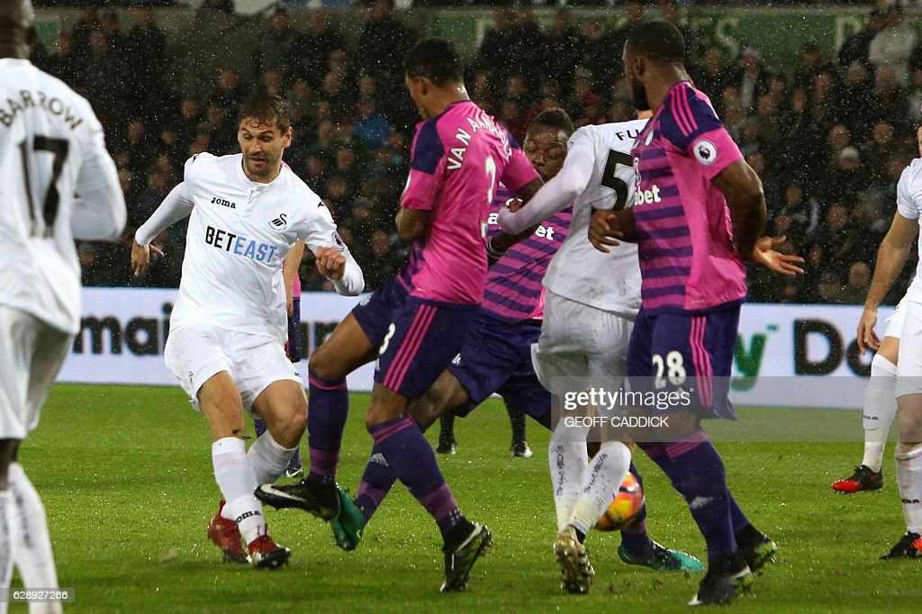 Swansea City's Spanish striker Fernando Llorente (L) shoots to score their second goal during the English Premier League football match between Swansea City and Sunderland at The Liberty Stadium in Swansea, south Wales on December 10, 2016. / AFP / Geoff CADDICK / RESTRICTED TO EDITORIAL USE. No use with unauthorized audio, video, data, fixture lists, club/league logos or 'live' services. Online in-match use limited to 75 images, no video emulation. No use in betting, games or single club/league/player publications. /