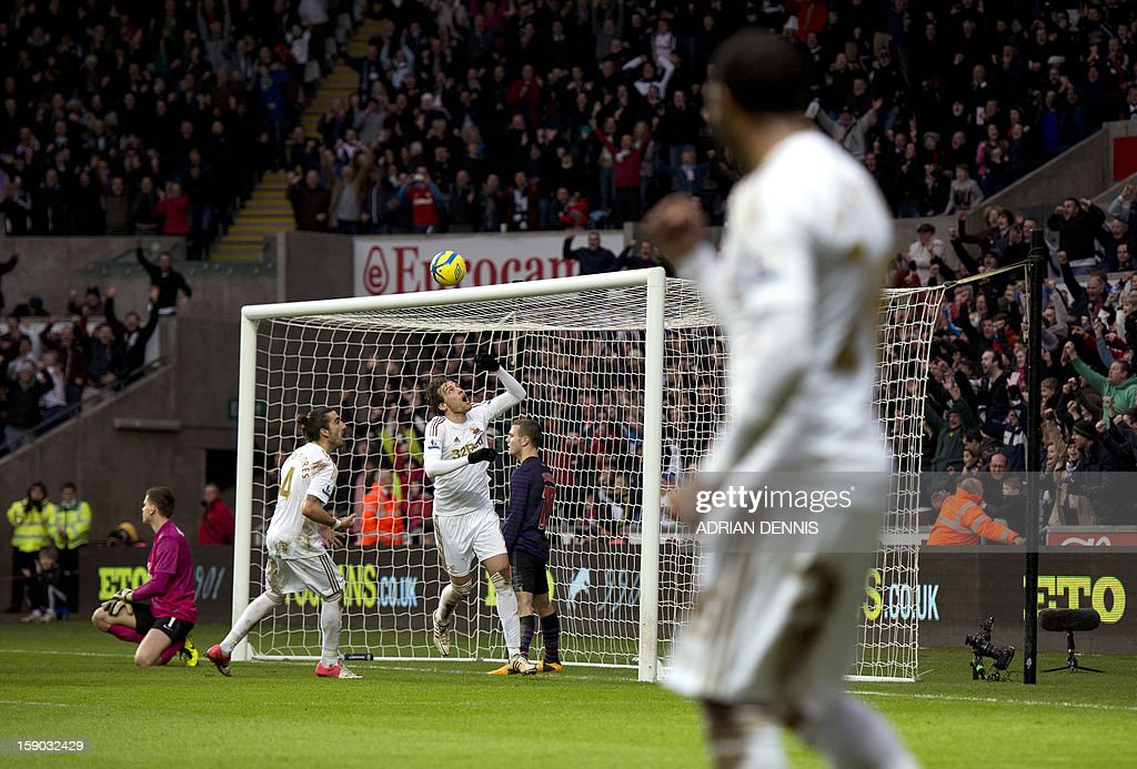 """Swansea City's Spanish striker Miguel Michu (C) retrieves the ball from the Arsenal goal after his teammae Danny Graham (not pictured) scored their second goal to equalise late in the game against Arsenal during the FA Cup third round football match at the Liberty Stadium in Swansea, Wales, on January 6, 2013. The game ended with a 2-2 draw. USE. No use with unauthorized audio, video, data, fixture lists, club/league logos or """"live"""" services. Online in-match use limited to 45 images, no video emulation. No use in betting, games or single club/league/player publications."""