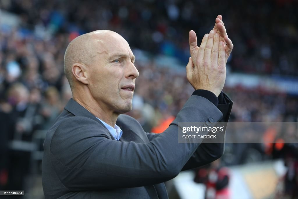 Swansea City's US manager Bob Bradley applauds supporters ahead of the English Premier League football match between Swansea City and Watford at The Liberty Stadium in Swansea, south Wales on October 22, 2016. / AFP PHOTO / Geoff CADDICK / RESTRICTED TO EDITORIAL USE. No use with unauthorized audio, video, data, fixture lists, club/league logos or 'live' services. Online in-match use limited to 75 images, no video emulation. No use in betting, games or single club/league/player publications. /