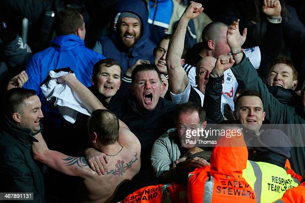 Swansea fans celebrate their third goal during the Barclays Premier League match between Swansea City and Cardiff City at the Liberty Stadium on...