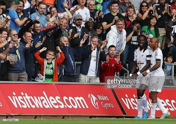 Swansea fans cheer as Swansea City's French striker Bafetimbi Gomis celebrates scoring a goal with Swansea City's Frenchborn Ghanaian striker Andre...