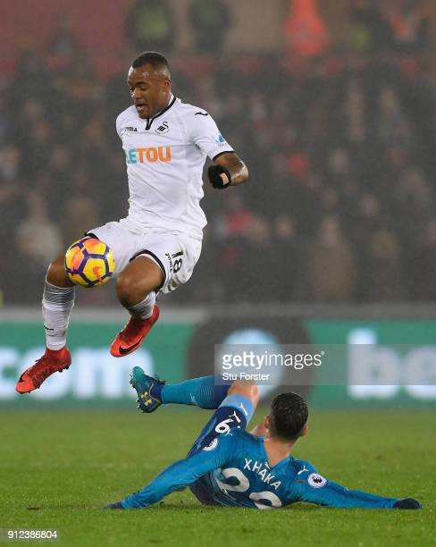 Swansea forward Jordan Ayew skips the challenge of Arsenal player Granit Xhaka during the Premier League match between Swansea City and Arsenal at...