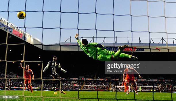 Swansea goalkeeper Michel Vorm dives at a shot by Demba Ba during the Barclays Premier league game between Newcastle United and Swansea City at St...