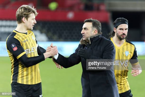 Swansea manager Carlos Carvalhal greets Glenn Loovens of Sheffield Wednesday during The Emirates FA Cup Fifth Round Replay match between Swansea City...