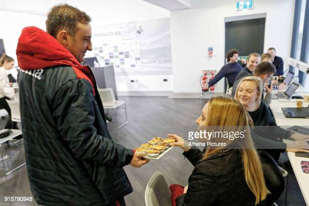Swansea Manager Carlos Carvalhal hands over Portuguese desserts to members of the press during the Swansea City Training and Press Conference at The...
