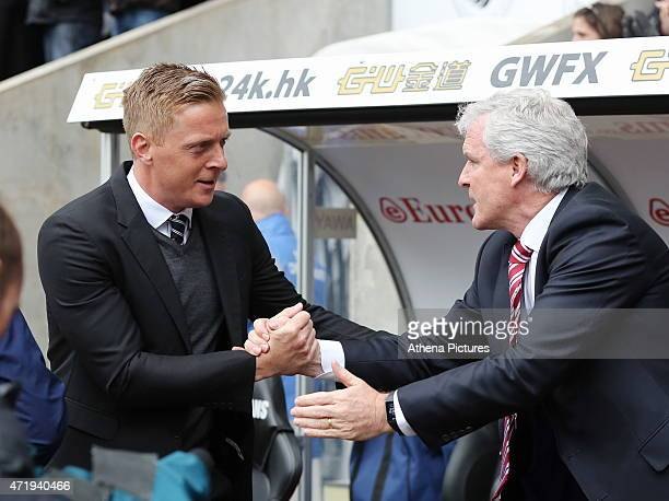 Swansea manager Garry Monk greets Stoke manager Mark Hughes in the dugout prior to the Premier League match between Swansea City and Stoke City at...