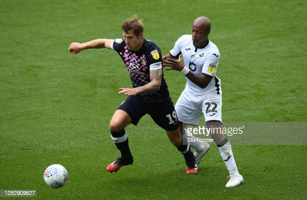 Swansea player Andre Ayew challenges James Collins of Luton during the Sky Bet Championship match between Swansea City and Luton Town at Liberty...