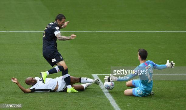 Swansea player Andre Ayew is denied by both Sonny Bradley and goalkeeper Simon Sluga during the Sky Bet Championship match between Swansea City and...