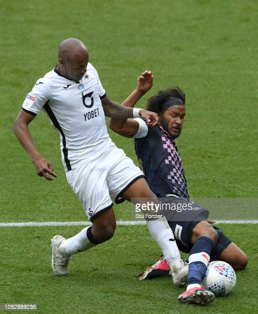Swansea player Andre Ayew is tackled by Luton player Izzy Brown during the Sky Bet Championship match between Swansea City and Luton Town at Liberty...