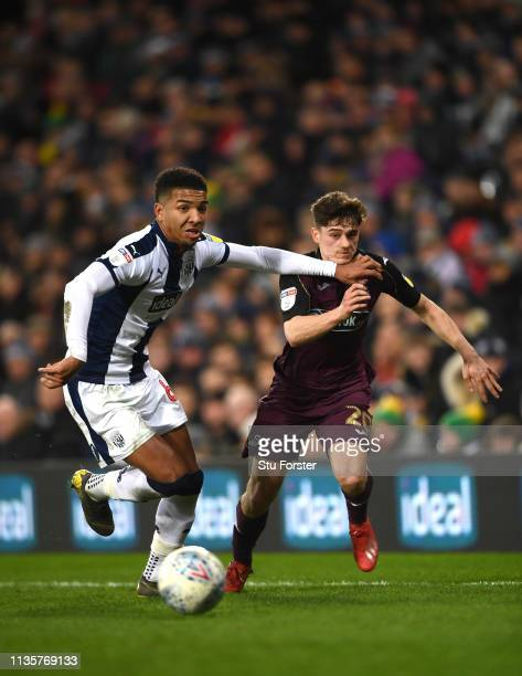 Swansea player Daniel James is held off the ball by WBA player Mason Holgate during the Sky Bet Championship match between West Bromwich Albion and...
