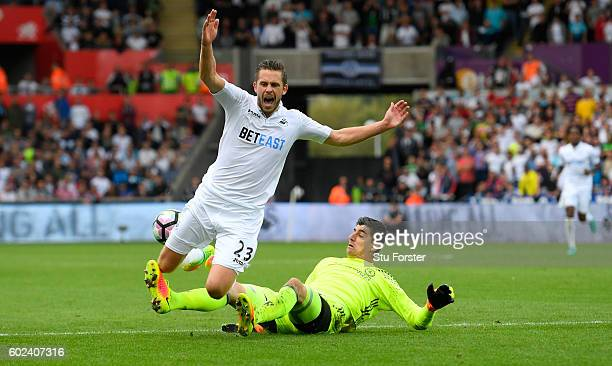 Swansea player Gylfi Sigurdsson is brought down by Thibaut Courtois for the Swansea penalty during the Premier League match between Swansea City and...