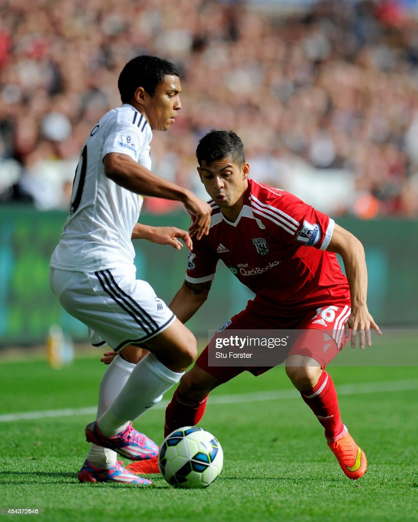 Swansea player Jefferson Montero (l) is challenged by Cristian Gamboa of West Brom during the Barclays Premier League match between Swansea City and West Bromwich Albion at Liberty Stadium on August 30, 2014 in Swansea, Wales.