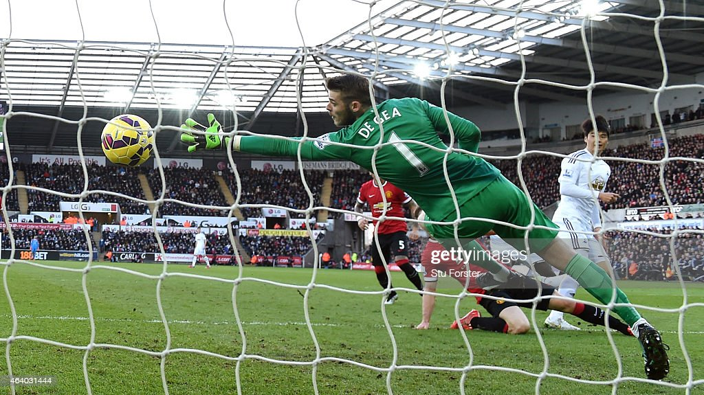 Swansea player Ki Sung - Yueng (r) scores the first Swansea goal past a diving David de Gea of Manchester United during the Barclays Premier League match between Swansea City and Manchester United at Liberty Stadium on February 21, 2015 in Swansea, Wales.