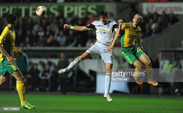 Swansea player Michu beats Aleksei Kozlov to the ball during the UEFA Europa League Group A match between Swansea City and FC Kuban Krasnodar at...
