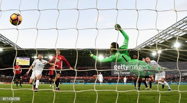 Swansea player Mike van der Hoorn heads the Swansea goal past goalkeeper David De Gea during the Premier League match between Swansea City and...