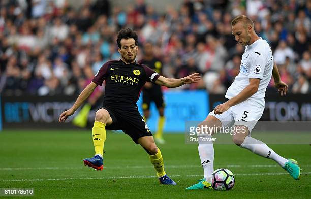 Swansea player Mike van der Hoorn is challenged by David Silva of Manchester City during the Premier League match between Swansea City and Manchester...