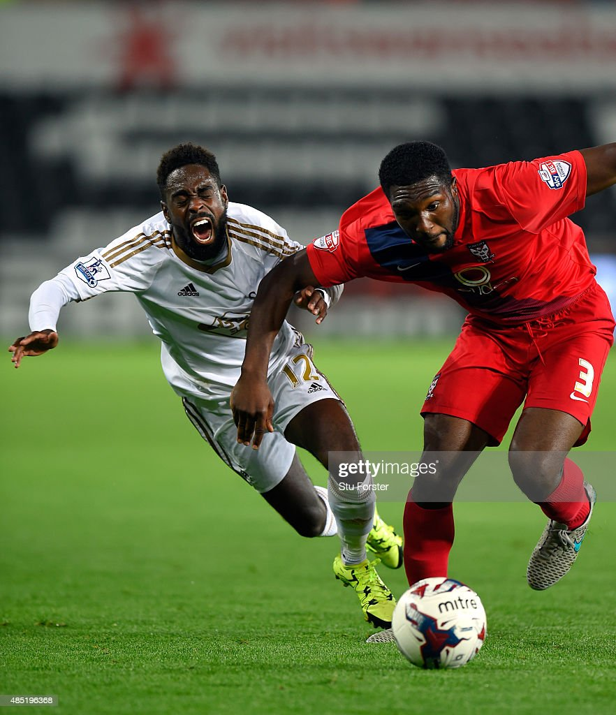 Swansea player Nathan Dyer (l) is challenged by Femi Ilesanmi of York during the Capital One Cup Second Round match between Swansea City and York City at Liberty Stadium on August 25, 2015 in Swansea, Wales.