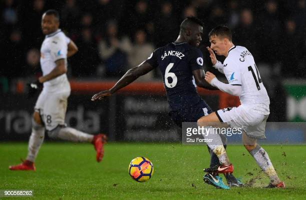 Swansea player Tom Carroll is challenged by Davinson Sanchez during the Premier League match between Swansea City and Tottenham Hotspur at Liberty...