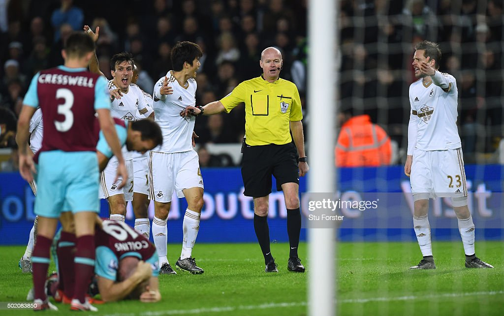 Swansea players appeal to referee Lee Mason after James Collins (ground) of West Ham appeared to handle the shot from Ki Sung-Yeung of Swansea City during the Barclays Premier League match between Swansea City and West Ham United at the Liberty Stadium on December 20, 2015 in Swansea, Wales.
