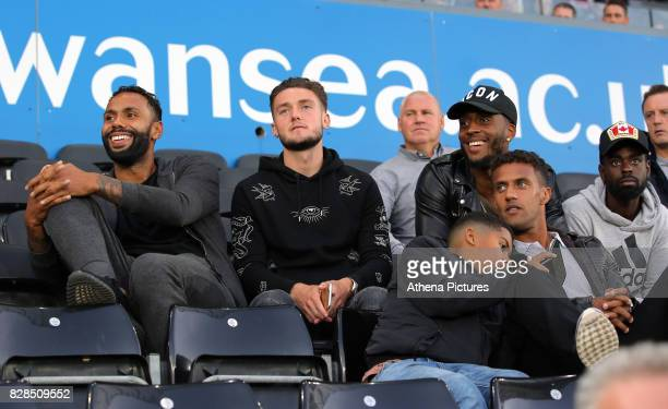 Swansea players Kyle Bartley Matt Grimes assistant coach Nigel Gibbs players Leroy Fer Wayne Routledge and Nathan Dyer watch the game during the...